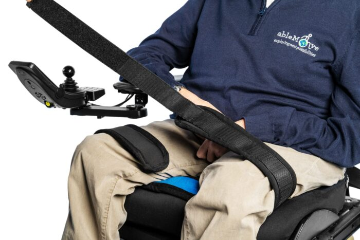 A wheelchair users legs are being shown sat in wheelchair with a leg strap securing the thighs of the legs together