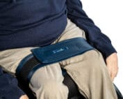 A wheelchair users legs are being shown sat in wheelchair with a leg strap securing the upper part of legs together