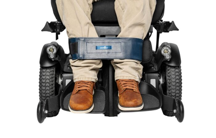 A wheelchair users legs are being shown sat in wheelchair with a leg strap securing the bottom of the legs together