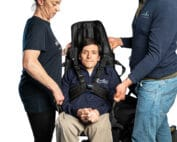 Two people are lifting a wheelchair user in a transfer sling which has a head rest. The wheelchair user is secured with a harness around their chest for extra safety