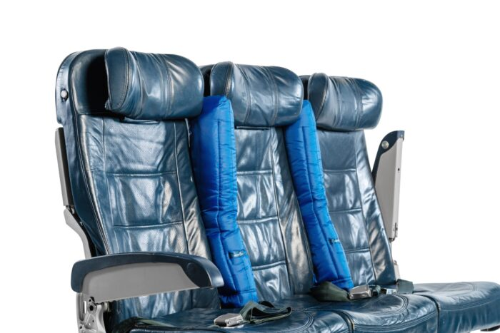 A picture of aircraft seats, with two blue padded arm covers, with the middle arm rests up