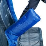 A blue padded arm cover is being placed over an arm rest of an aircraft by special assistance for a wheelchair user