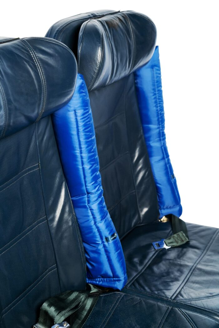 Two blue padded covers are slotted over to foldable arm rests on aircraft seats in an upright position for wheelchair users