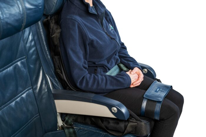 A wheelchair user is sat onto of a sling and a cushion with a leg strap around their thighs on a set of aircraft seats