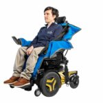 Josh Wintersgill sat in his powered wheelchair with an ableSling Lite (a transfer sling) whilst sat on an ableDry (wheelchair cover to keep the seating area dry).
